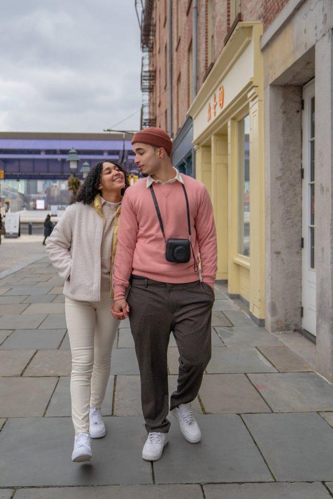 cheerful hispanic couple holding hands and walking on street